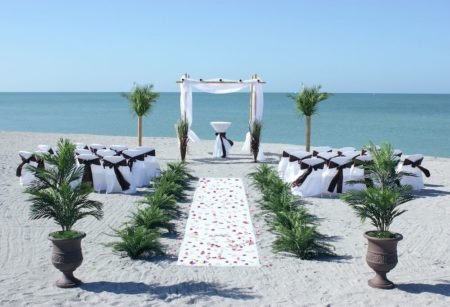 Florida sun weddings white chuppah with white chairs and brown sashes   Florida Beach Wedding