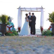 Florida sun weddings white chuppah with red sashes on chairs | Florida Beach Wedding