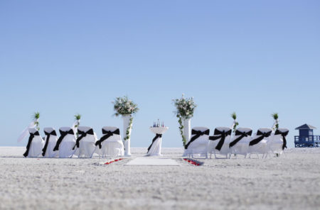 white columns with white chairs and black sashes   beach wedding in florida