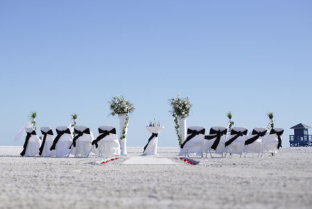 white columns with white chairs and black sashes | beach wedding in florida