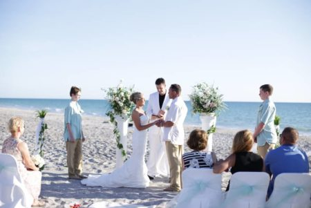 white columns with white chairs and aqua sashes | beach wedding in florida