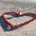 red rose petal heart in the sand on the beach | florida sun weddings