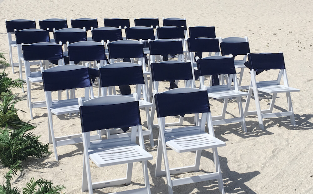 resin chairs with navy blue sashes beach wedding decor florida