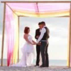 beach wedding ceremony under whispering sands trellis with pink orange and yellow | floridasunweddings.com