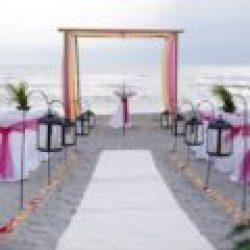 whispering sands beach wedding package in pink, yellow, orange with black lanterns on shepherd's hooks | floridasunweddings.com